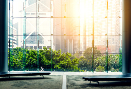 Glass office building with sunlight coming in and green trees